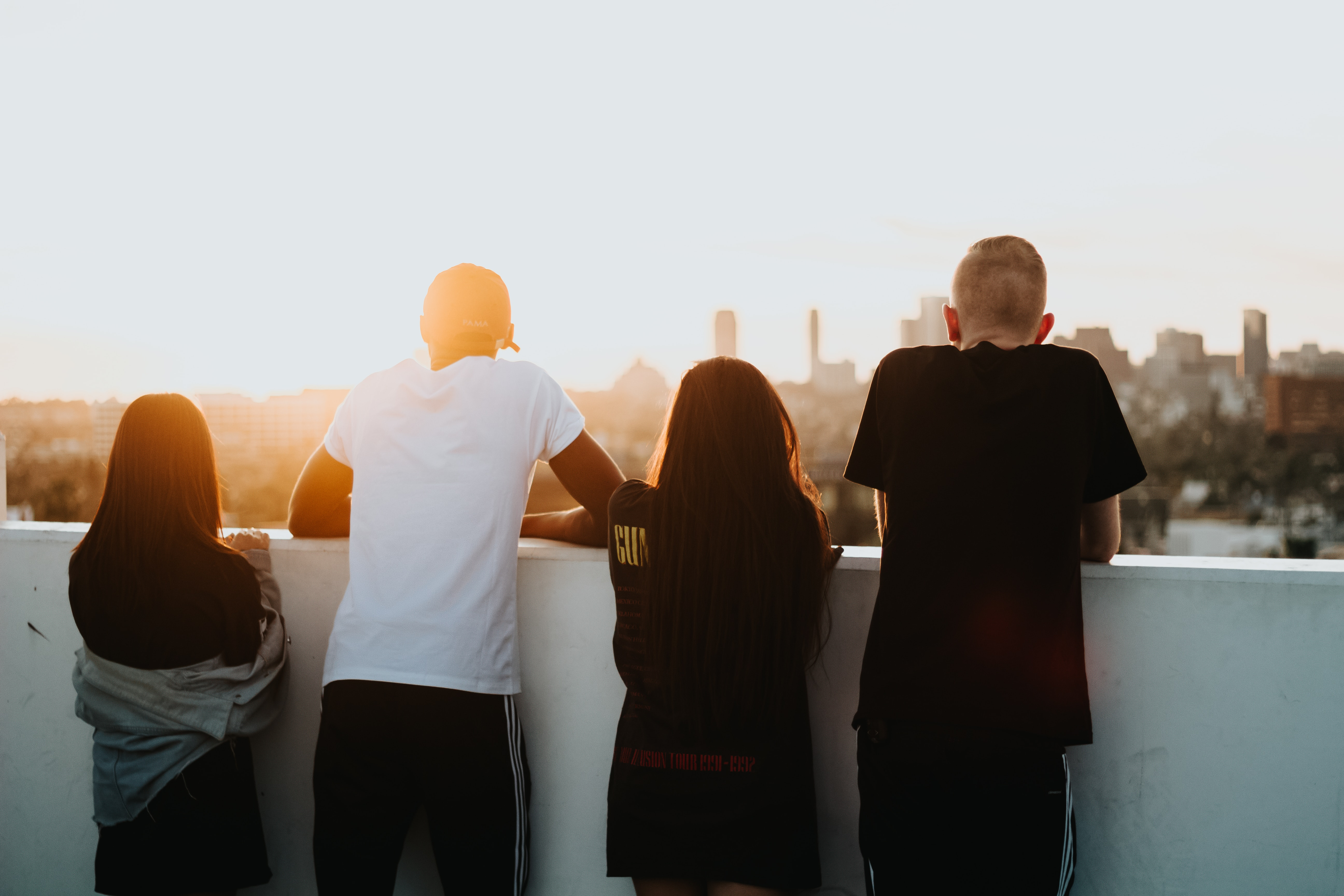 Four young people standing at a wall looking at a sunset