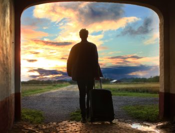 Man standing outside with a suitcase
