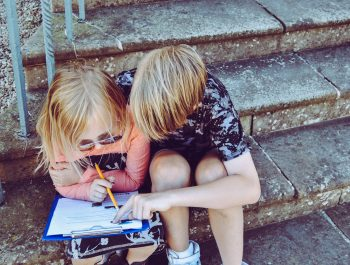 Two children drawing on a piece of paper